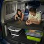 Pärchen liegt nachts bei geöffneter Heckklappe auf Schlafplatz in Campingmobil mit eingeschalteter Innenbeleuchtung