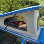 Aufgestelltes Dach eines Campingmobils mit Schlafkoje in der eine weibliche Person liegt