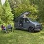 grauer VW Van im Grünen mit aufgestelltem Dach, daneben Campingtisch mit Stühlen