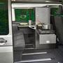 Blick durch geöffnete Seitentür von Campingmobil auf ausziehbares Küchenmodul mit Kochplatte