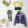 Kleidungsstücke, Acessoires und Schuhe in Wandregalen und auf einem Tisch drapiert