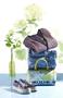 Tasche, Jeans und Strickjacke gestapelt neben einem Paar Schuhe mit Blumendeko